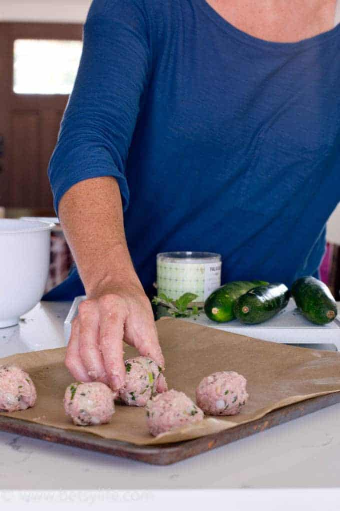 Hand placing formed turkey meatballs onto a baking sheet lined with parchment paper