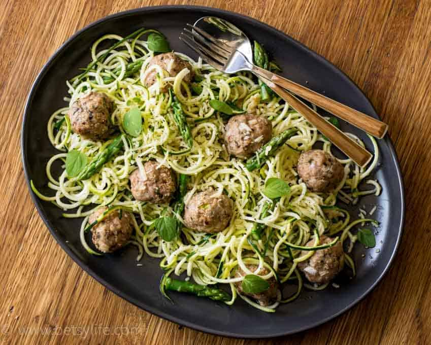 Turkey Meatballs with Zucchini Spaghetti on a brown oval platter with a fork and a spoon