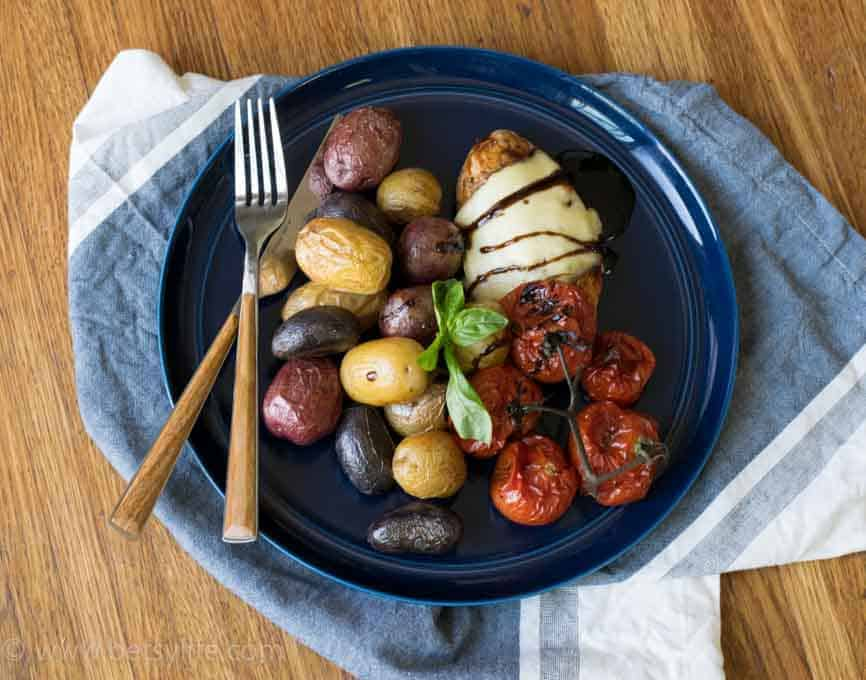 blue plate on a blue and white napkin. Chicken breast topped with melted cheese, roasted rainbow baby potatoes and roasted tomatoes. Fork and knife with wooden handles.