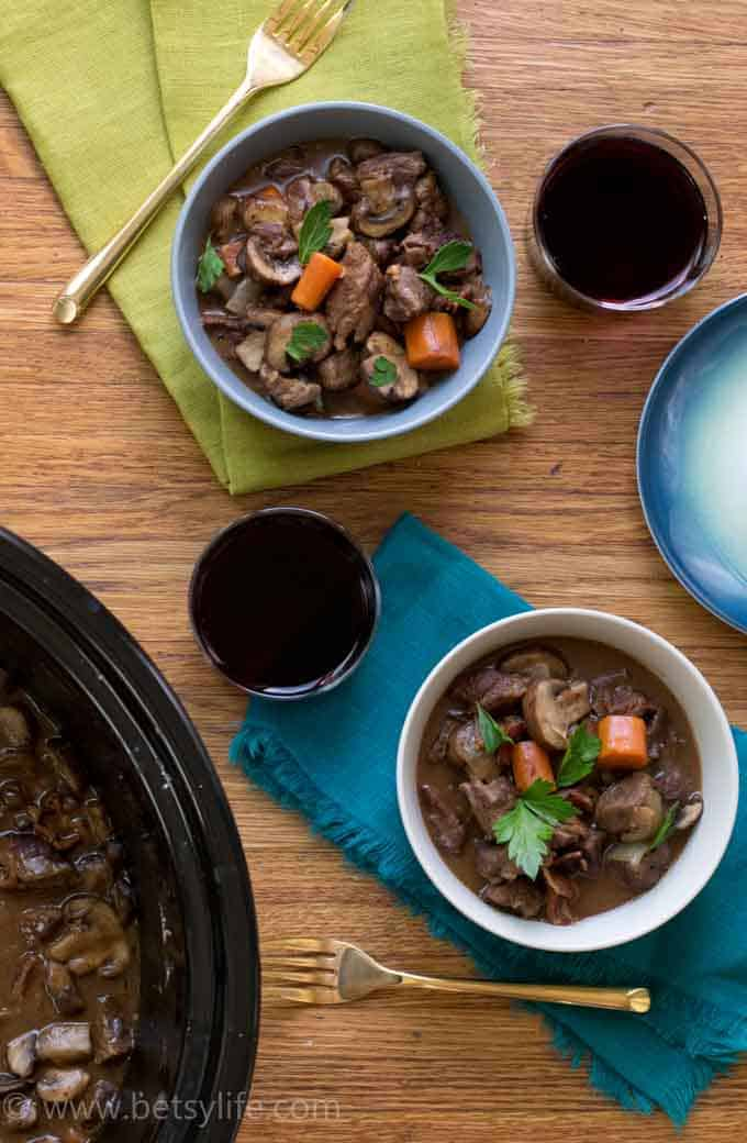 Crock Pot Beef Bourguignon served in two bowls with glasses of red wine, colorful napkins and gold forks