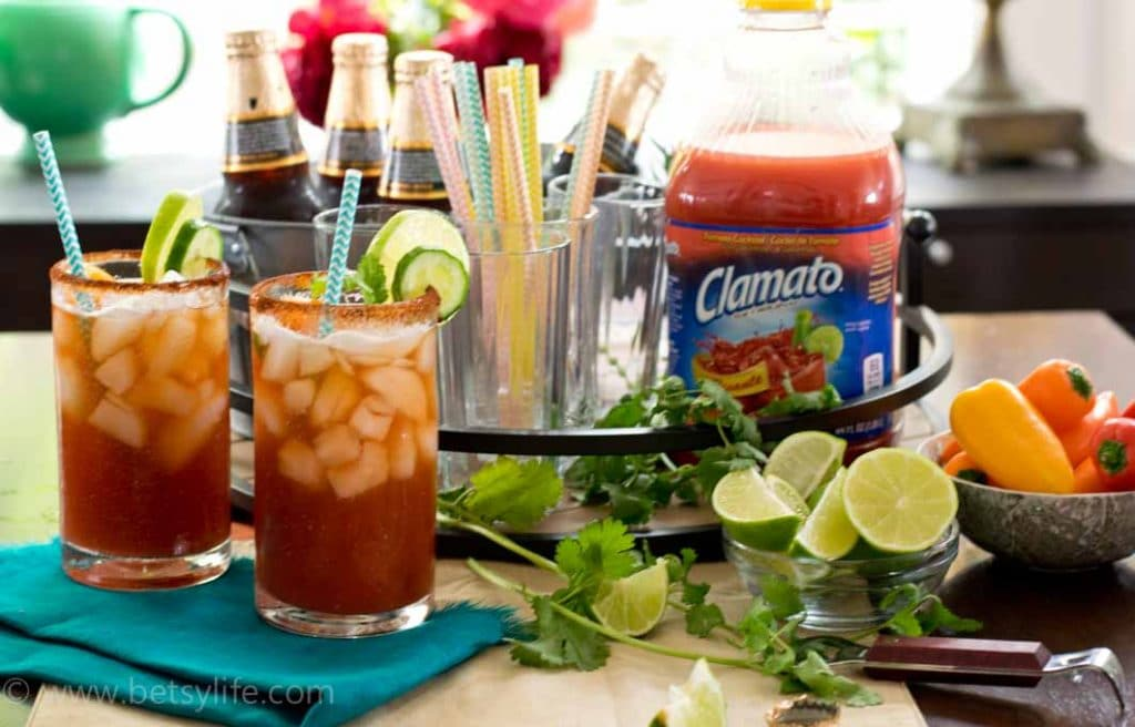 Two chipotle micheladas on a blue napkin next to a bar set up of michelada ingredients