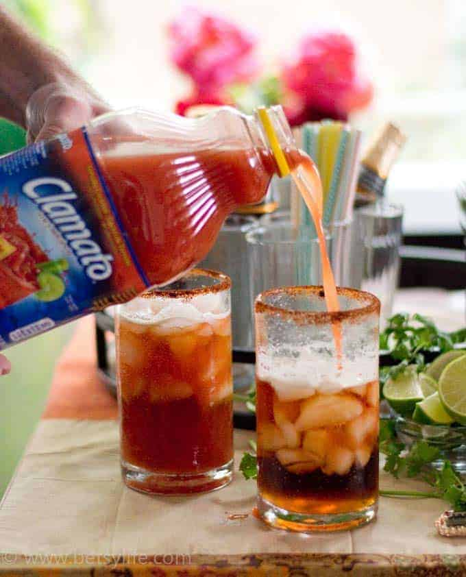 Clamato being poured into a glass of Michelada