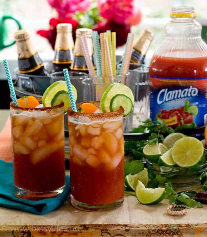 Two glasses of chipotle micheladas fully garnished with limes and cucumbers next to a bar set up with remaining ingredients