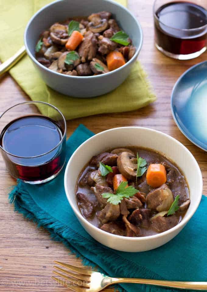 Crock Pot Beef Bourguignon served in two bowls with red wine glasses and colorful napkins