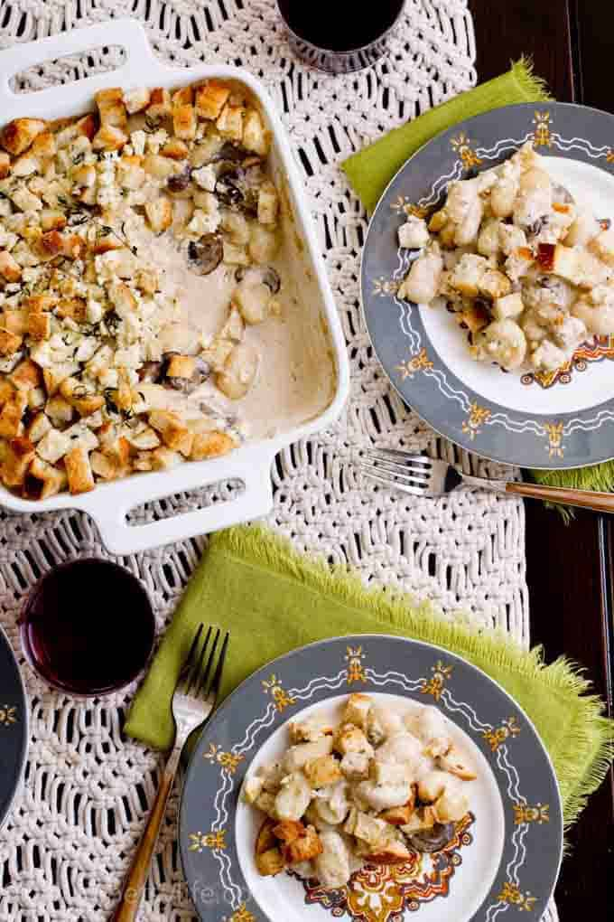 gnocchi gratin in a square dish next to two servings on patterned gray plates and a macrame table runner