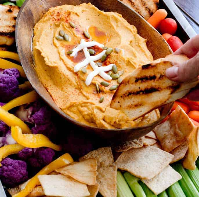 crostini dipping into a football shaped bowl full of pumpkin hummus
