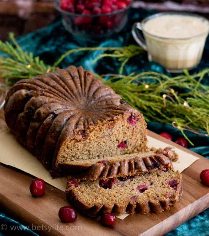Cranberry Eggnog Loaf Cake sliced on a wooden board with greenery and a cup of eggnog in the background