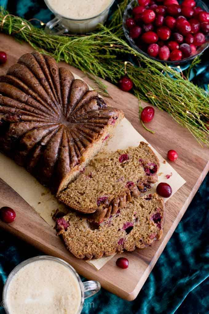 Detail of a slice of Cranberry Eggnog Loaf Cake on a wooden board with cranberries and greenery scattered around