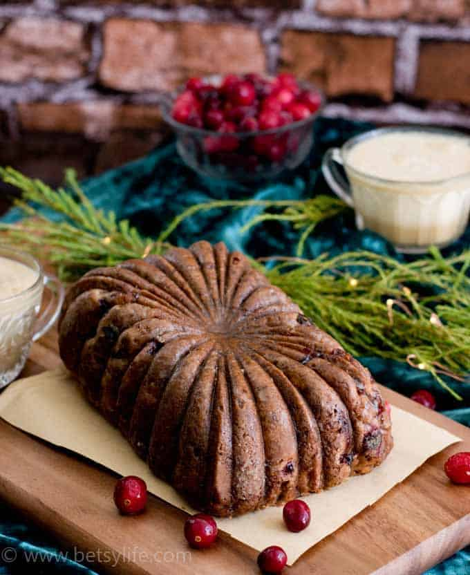 Cranberry Eggnog Loaf Cake on a wooden board with a brick background and cranberries scattered around