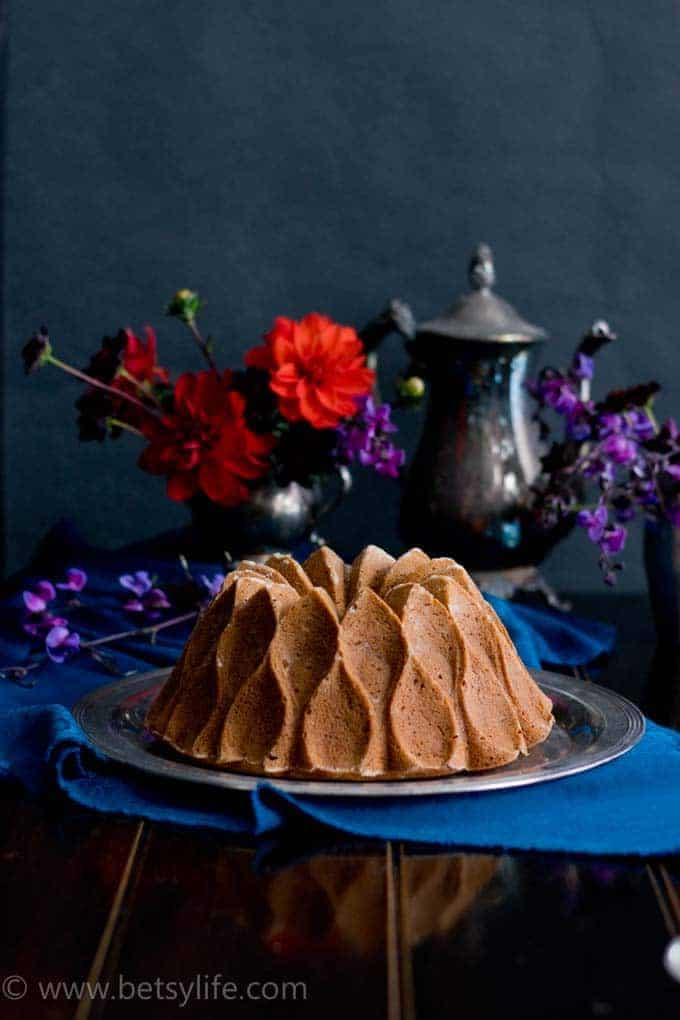 Sweet Potato Bourbon Bundt Cake on a dark table with a blue linen underneath