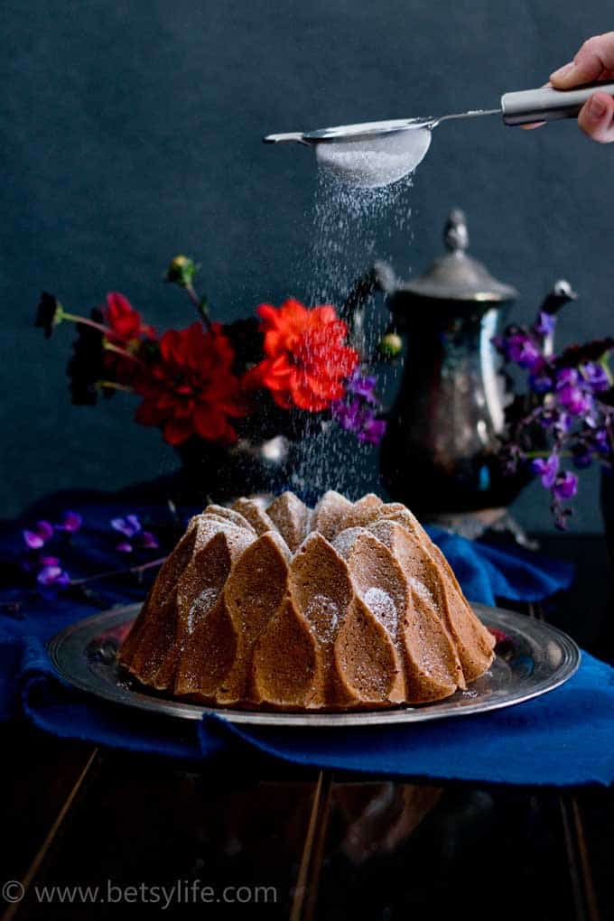 Bourbon Sweet Potato Bundt Cake being dusted with powdered sugar