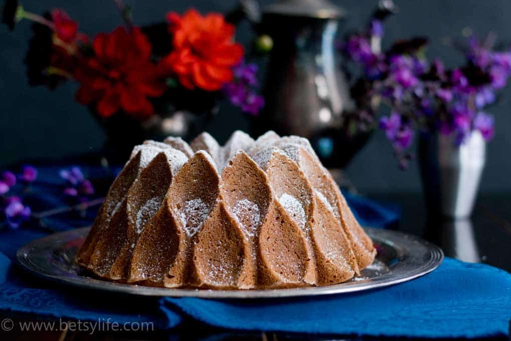Bourbon Sweet Potato Bundt Cake covered in powdered sugar with flowers in the background