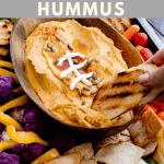 crostini dipping into a football shaped bowl of pumpkin hummus