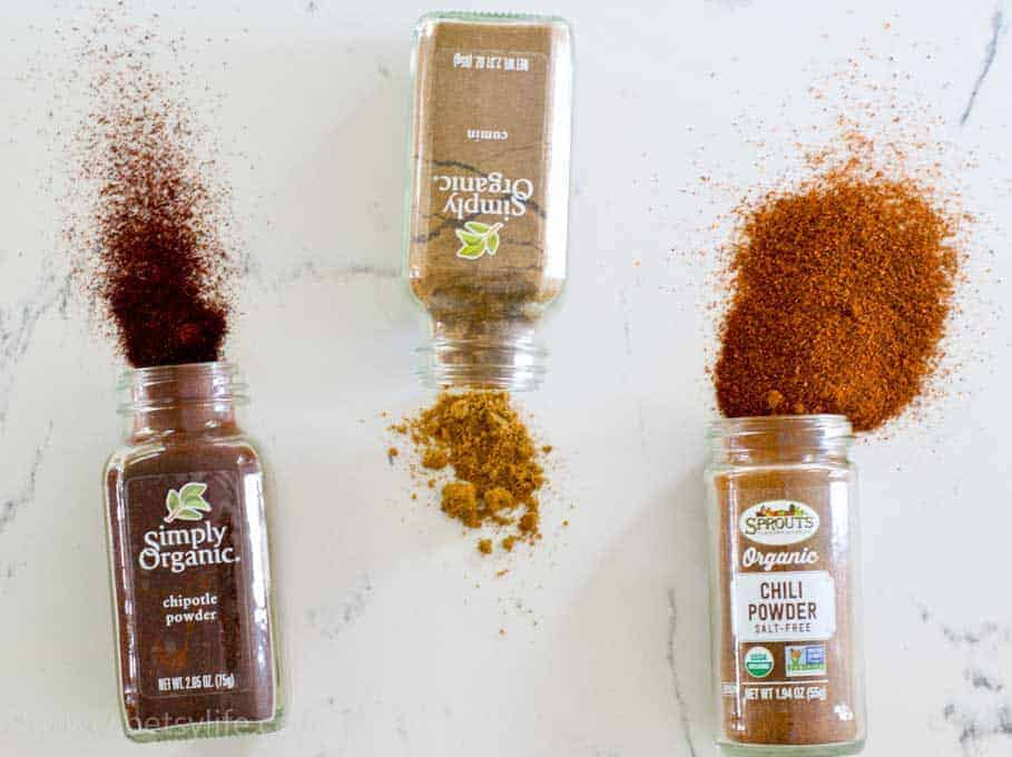 chipotle chili powder, cumin and chili powder spilled on a counter
