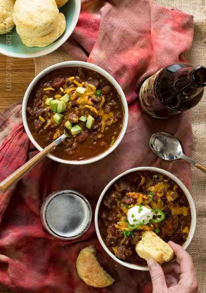 two bowls of Spicy Beef Beer Chili with cornbread being dipped in