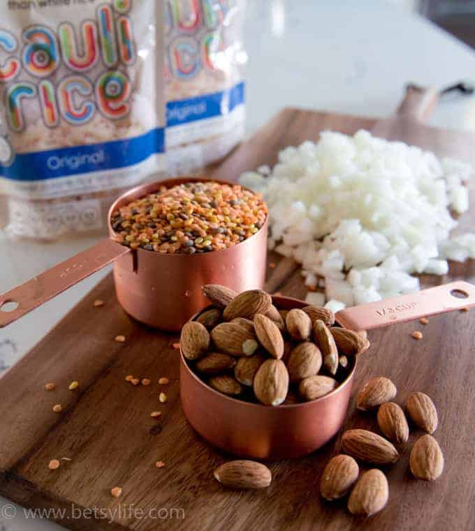 Measuring cups full of lentils and almonds with chopped onions in the background