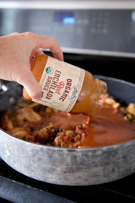 Jar of red enchilada sauce pouring into a large skillet with beans and chicken