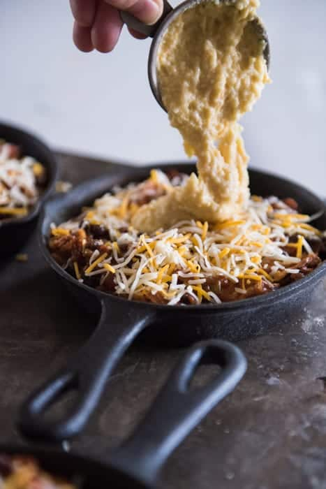 measuring cup of cornbread batter being poured over the top of a mini cast iron skillet filled with enchilada mix and shredded cheese
