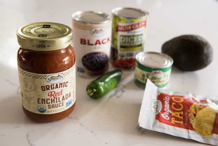 jar of red enchilada sauce, can of black beans, can of diced tomatoes, can of diced green chiles, packet of taco seasoning, jalapeno pepper and avocado on a white counter