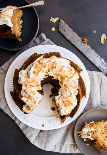 Dark background. carrot Bundt cake on a white plate with two slices removed. Slices sitting on a dark plate with a fork and a tan plate with no fork. Slicing knife on the side