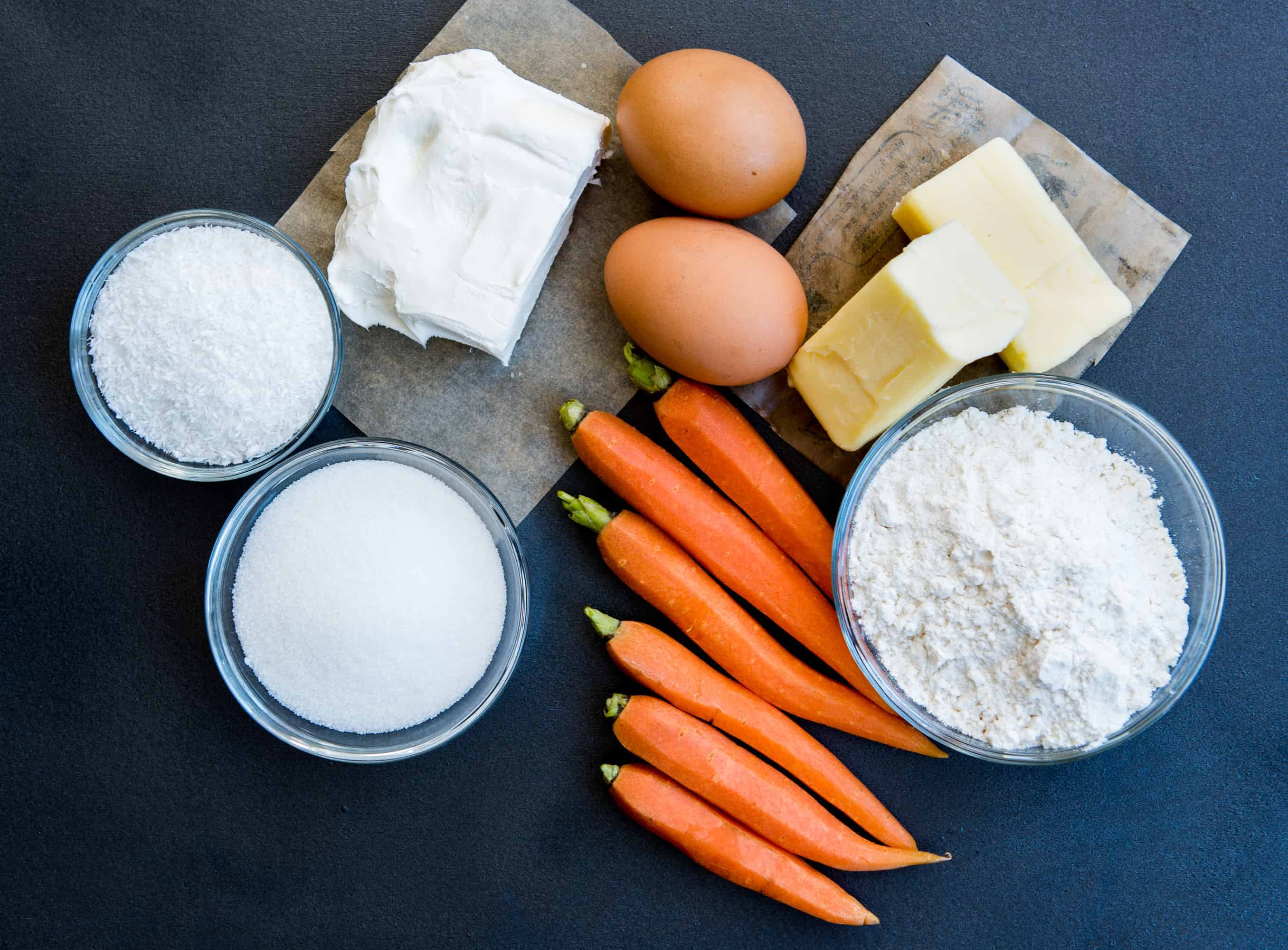 dark background. Ingredients laid out. Baby carrots, two eggs, two sticks of butter, block of cream cheese and small bowls filled with sugar, flour, and coconut flakes