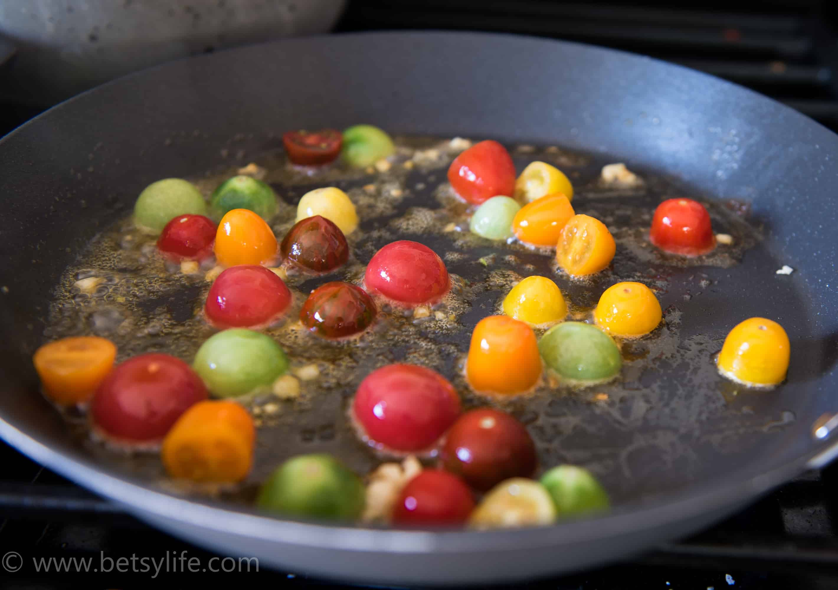 Shallow frying pan with cherry tomato halves roasting with garlic