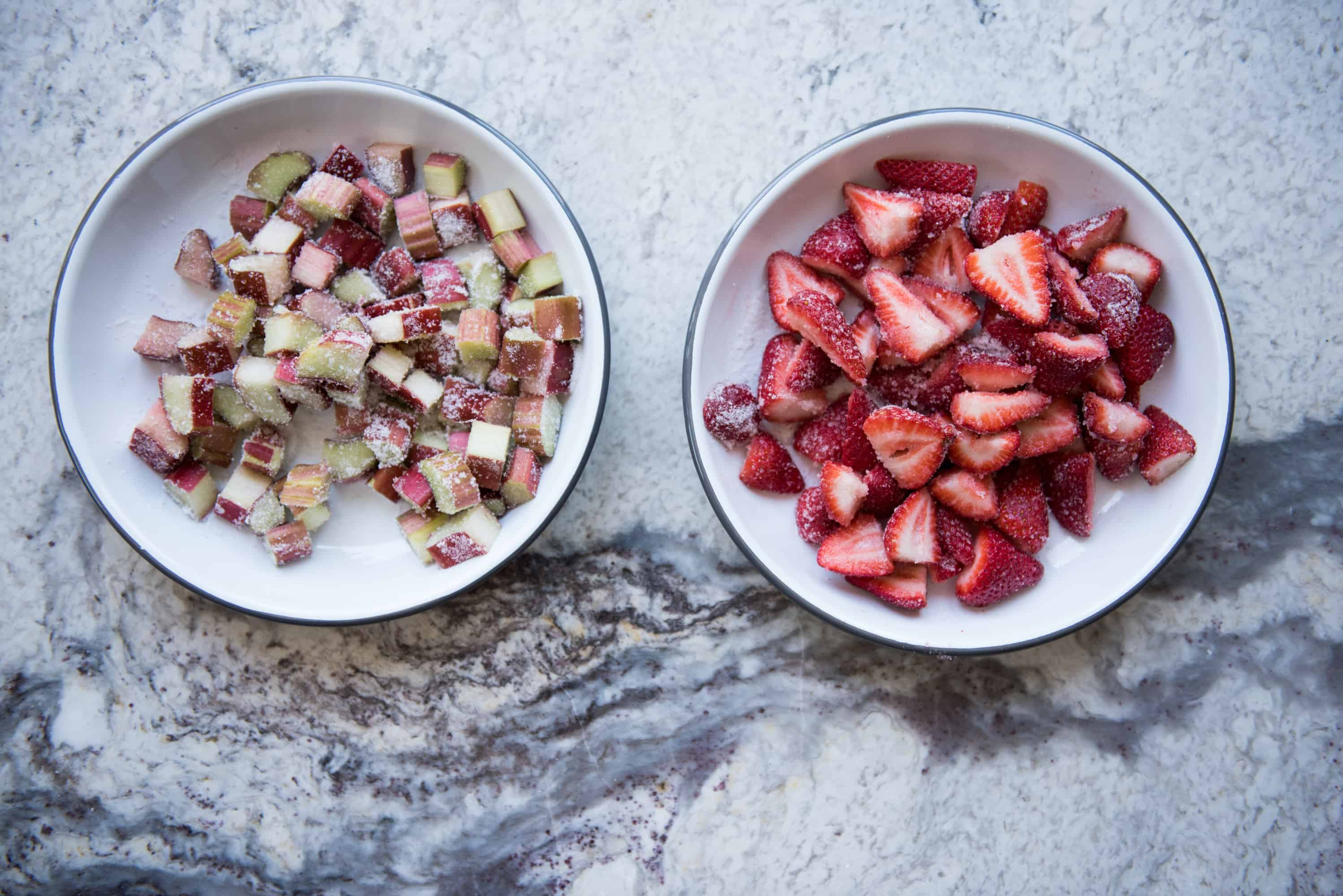 overhead of two white bowls. The bowl on the left contains chopped rhubarb and sugar and the bowl on the right contains chopped strawberries and sugar