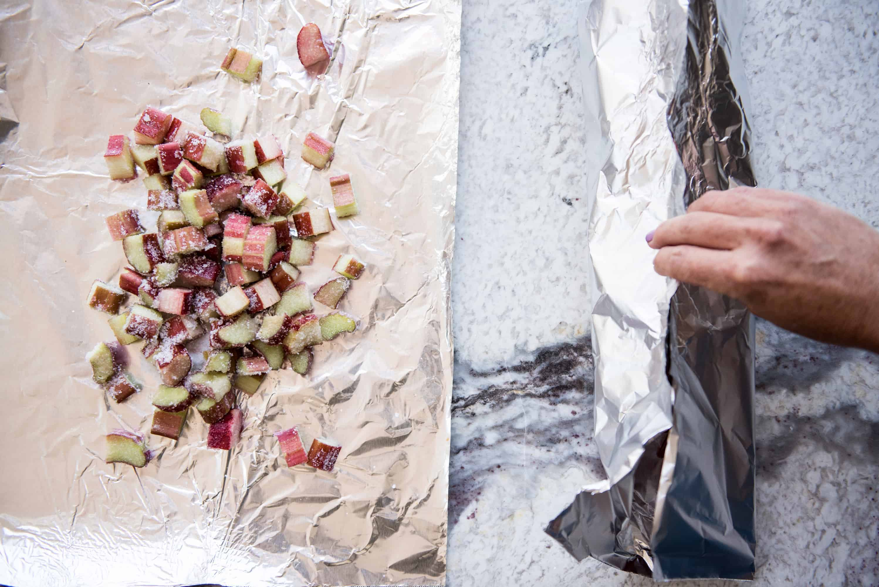 overhead shot of foil packets containing chopped rhubarb and strawberries being folded up