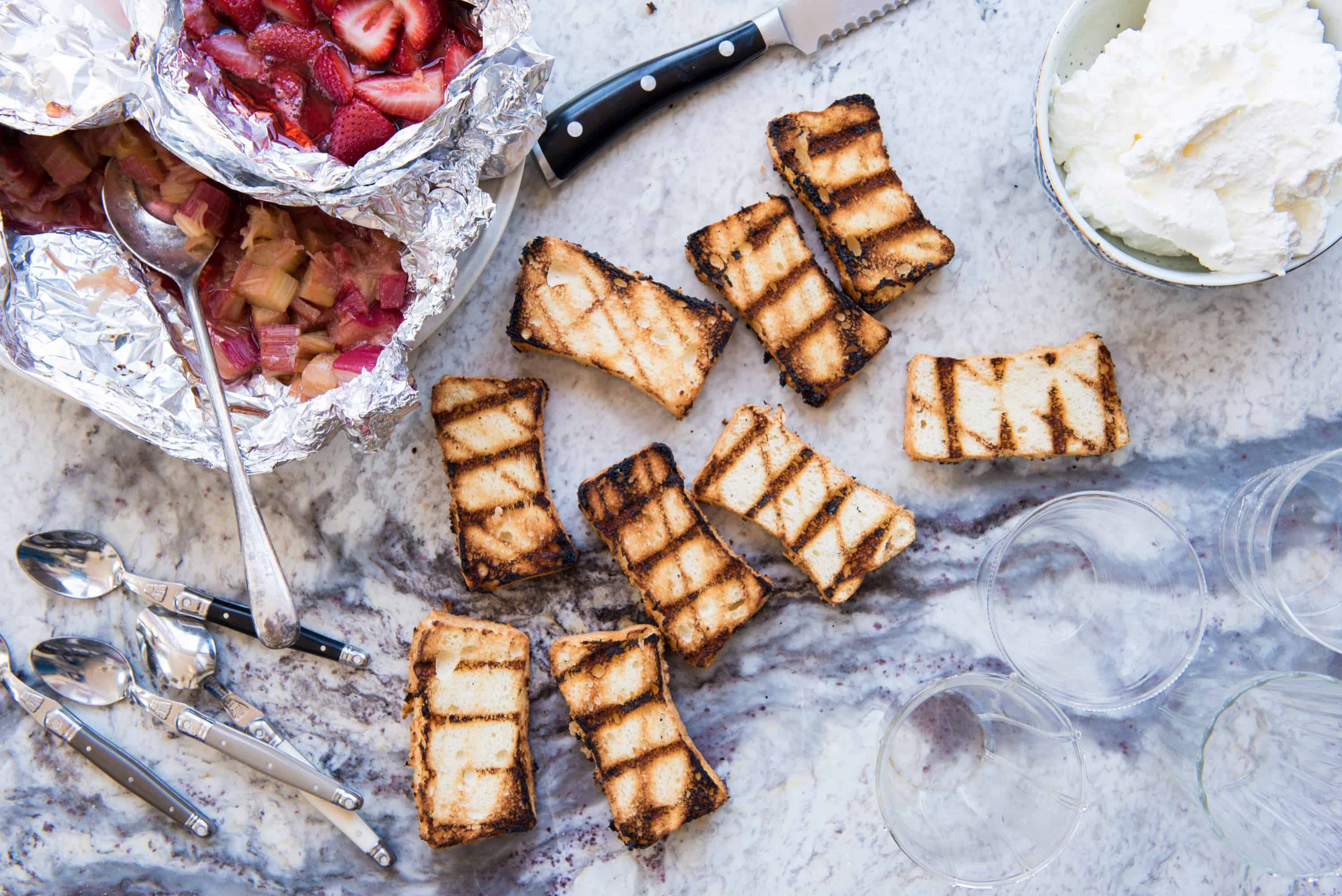overhead shot of slices of grilled angel food cake, a bowl of whipped cream in the upper right corner and two foil packets filled with grilled strawberries and grilled rhubarb in the top left corner. Spoons and empty glasses on the side.