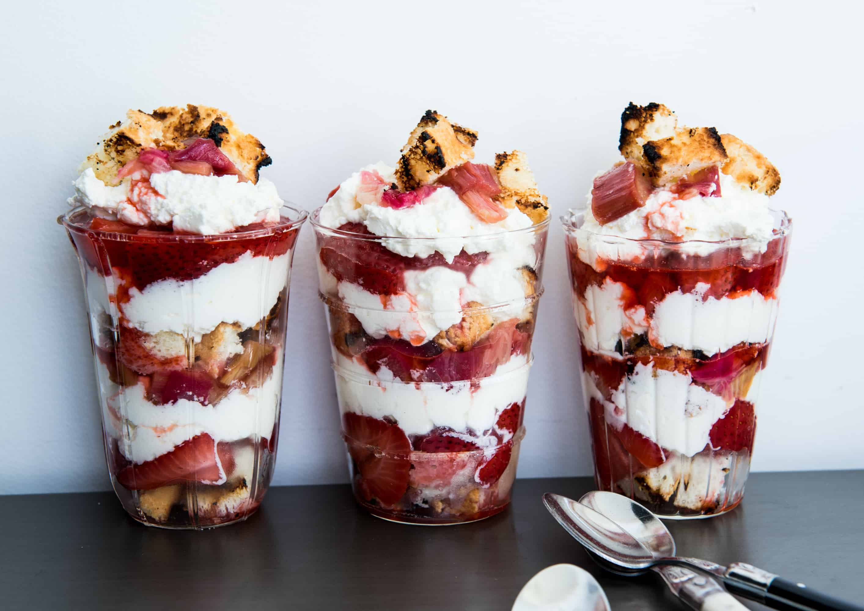 three layered rhubarb strawberry parfaits in clear glasses in a row. Layers of grilled angel food cake, grilled strawberries, grilled rhubarb and whipped cream