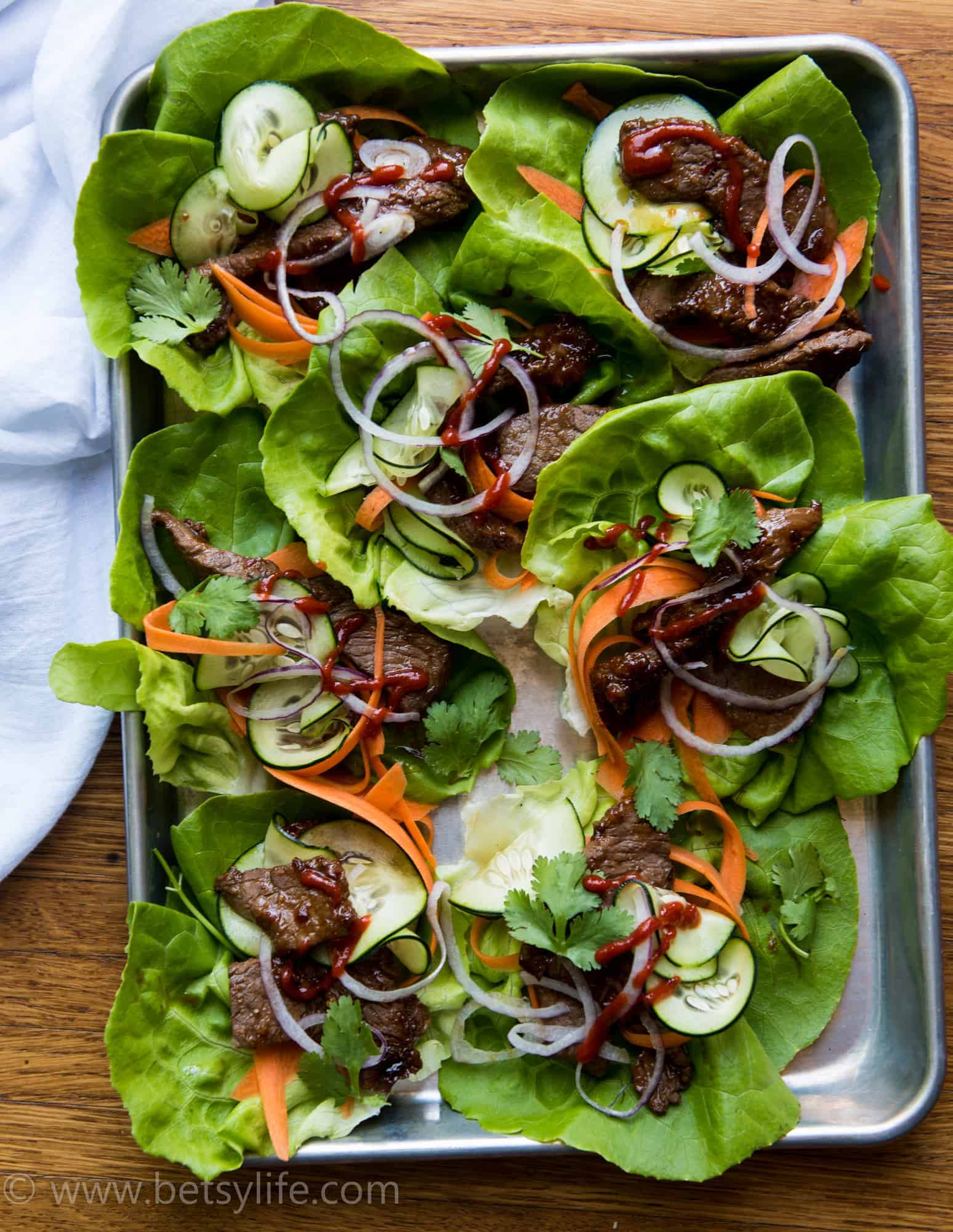 overhead view of a sheet pan filled with lettuce wraps. Lettuce wraps contain steak, thinly sliced carrots, cucumbers, cilantro leaves, and red onion. Drizzled with cilantro.