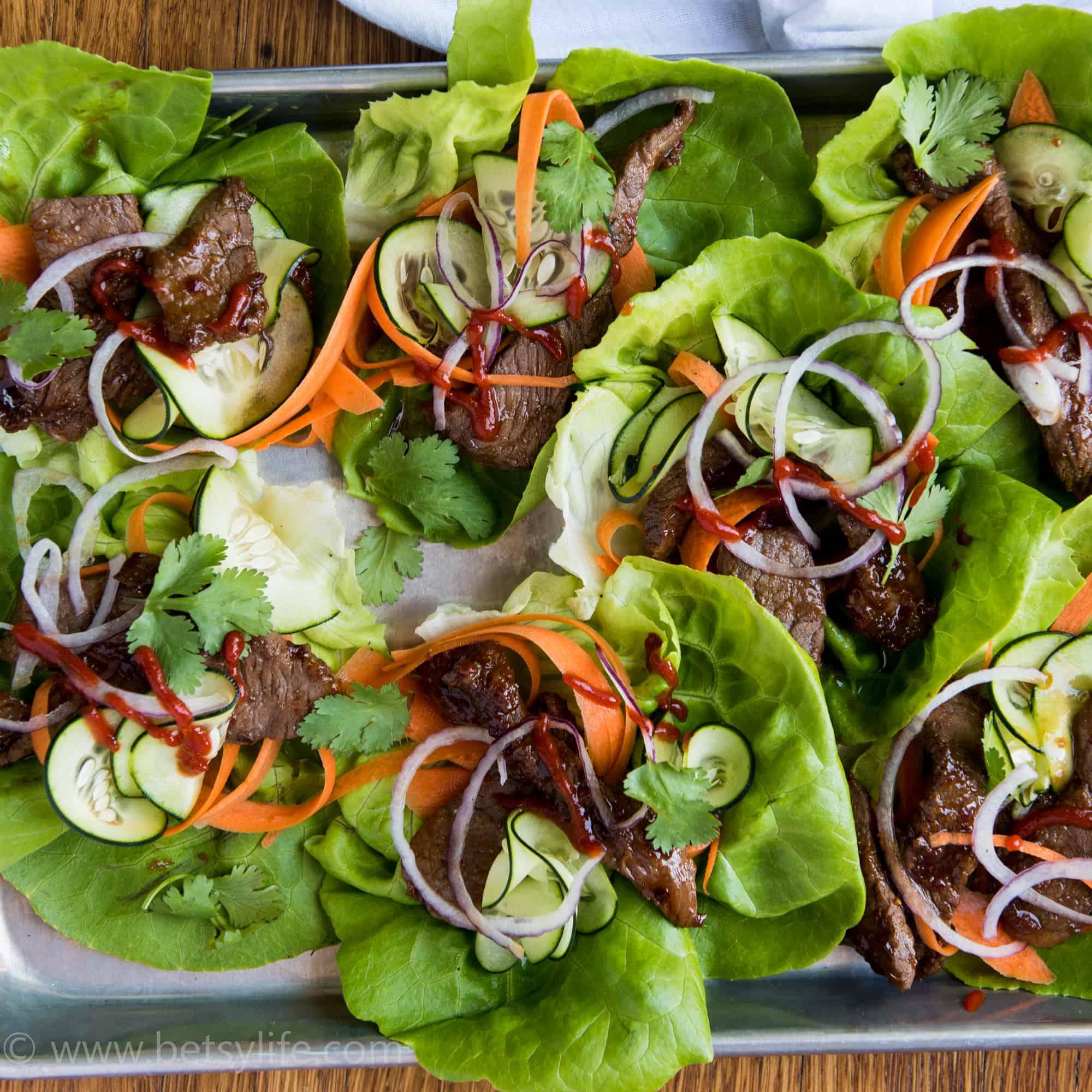 Overhead of a sheet pan filled with healthy lettuce wraps filled with steak, thinly shaved carrots, cucumbers and red onions. Drizzle of sriracha sauce over the top