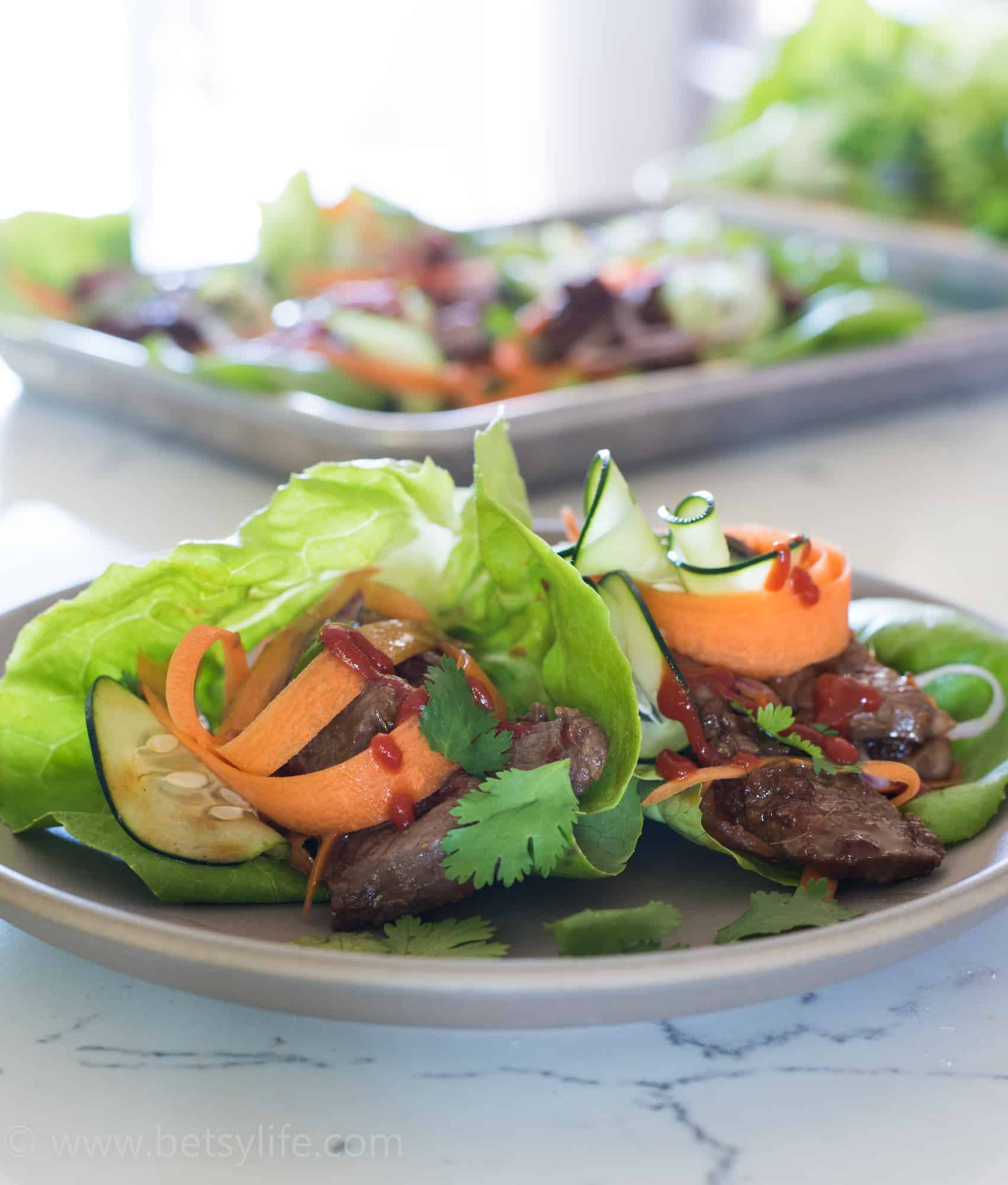 Two healthy lettuce wraps piled high with marinade strips of steak, thinly sliced carrots, cucumbers and red onions, cilantro leaves and Sriracha drizzle