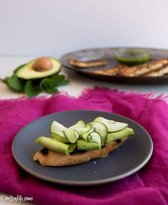 slice of grilled bread on a dark gray plate on top of a pink napkin. Bread is topped with thinly sliced avocado and cucumber