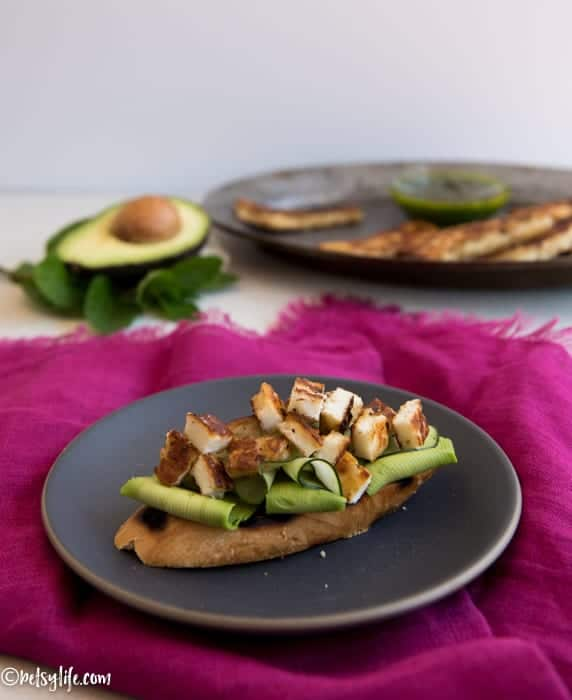 grilled bread topped with thinly sliced avocado, cucumber and grilled halloumi cheese chunks. Toast is on a dark gray plate on a pink napkin