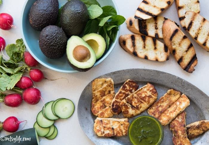 overhead photo of whole radishes, bowl of avocados, one is sliced, grilled bread, sliced cucumbers and a metal plate of grilled halloumi cheese