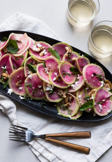 Overhead photo of thinly sliced watermelon radish salad on an oval black plate on top of a natural linen napkin. Light colored background. Two glasses of white wine in the upper right corner and two forks with wooden handles in the lower left corner