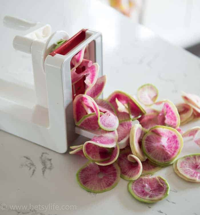 pile of watermelon radishes coming out of a spiralizer