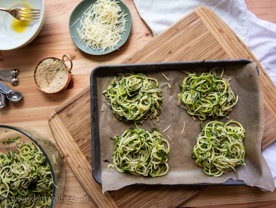 overhead photo of spiralized zucchini nests prepped on a baking sheet lined wth parchment paper. Additional ingredients around the perimeter: grated parmesan, breadcrumbs, eggs