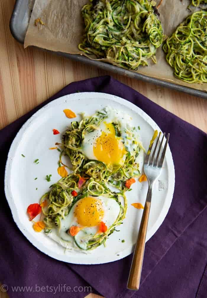 Two Spiralized zucchini nests on a white plate with runny yolk eggs on top. Fork to the right and a purple napkin underneath. Tray with additional spiralized zucchini nests peaking out from the top right corner