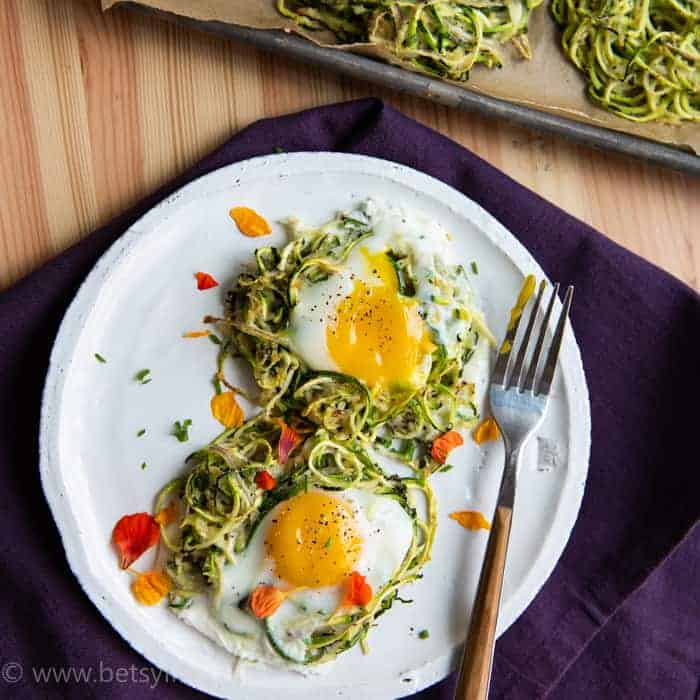 Two Spiralized zucchini nests on a white plate with runny yolk eggs on top. Fork to the right and a purple napkin underneath