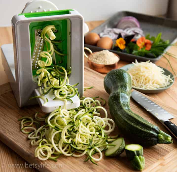 Zucchini being spiralized on a white plastic machine. Tray of additional ingredients out of focus in the background