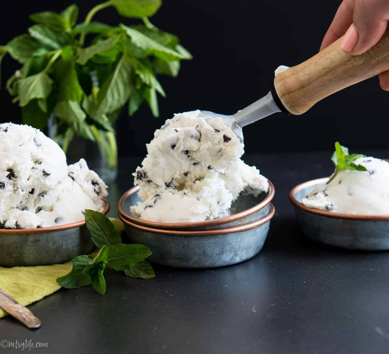 hand scooping mint chip ice cream into one of three metal bowls. Fresh mint in the background