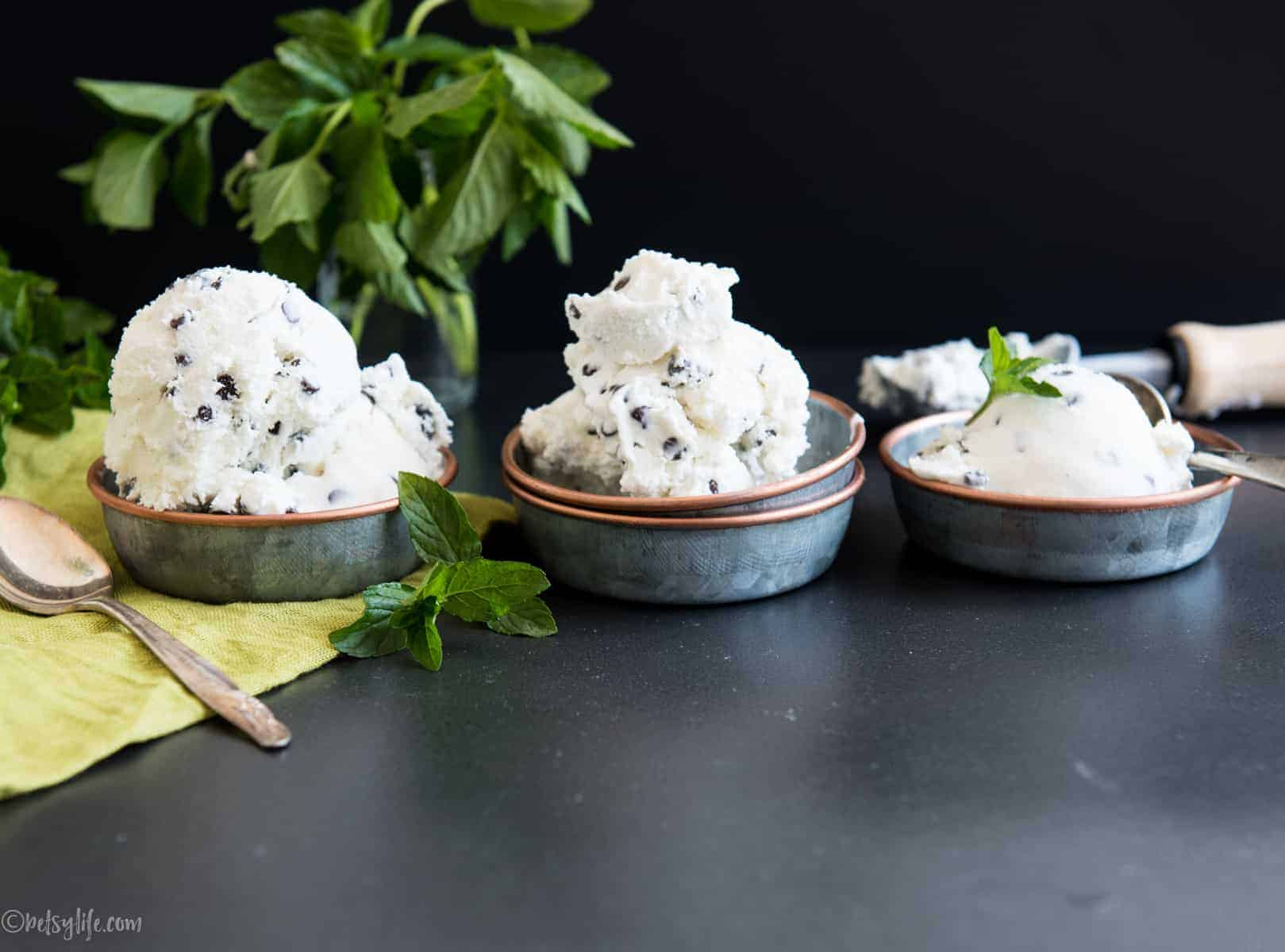 three metal bowls of mint chip ice cream with fresh mint in the background