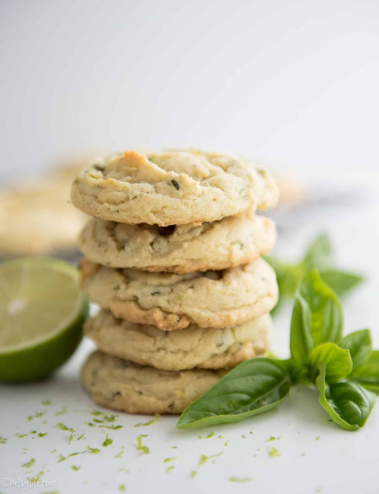 Stack of 5 basil lime sugar cookies with half a lime and a sprig of basil on the side