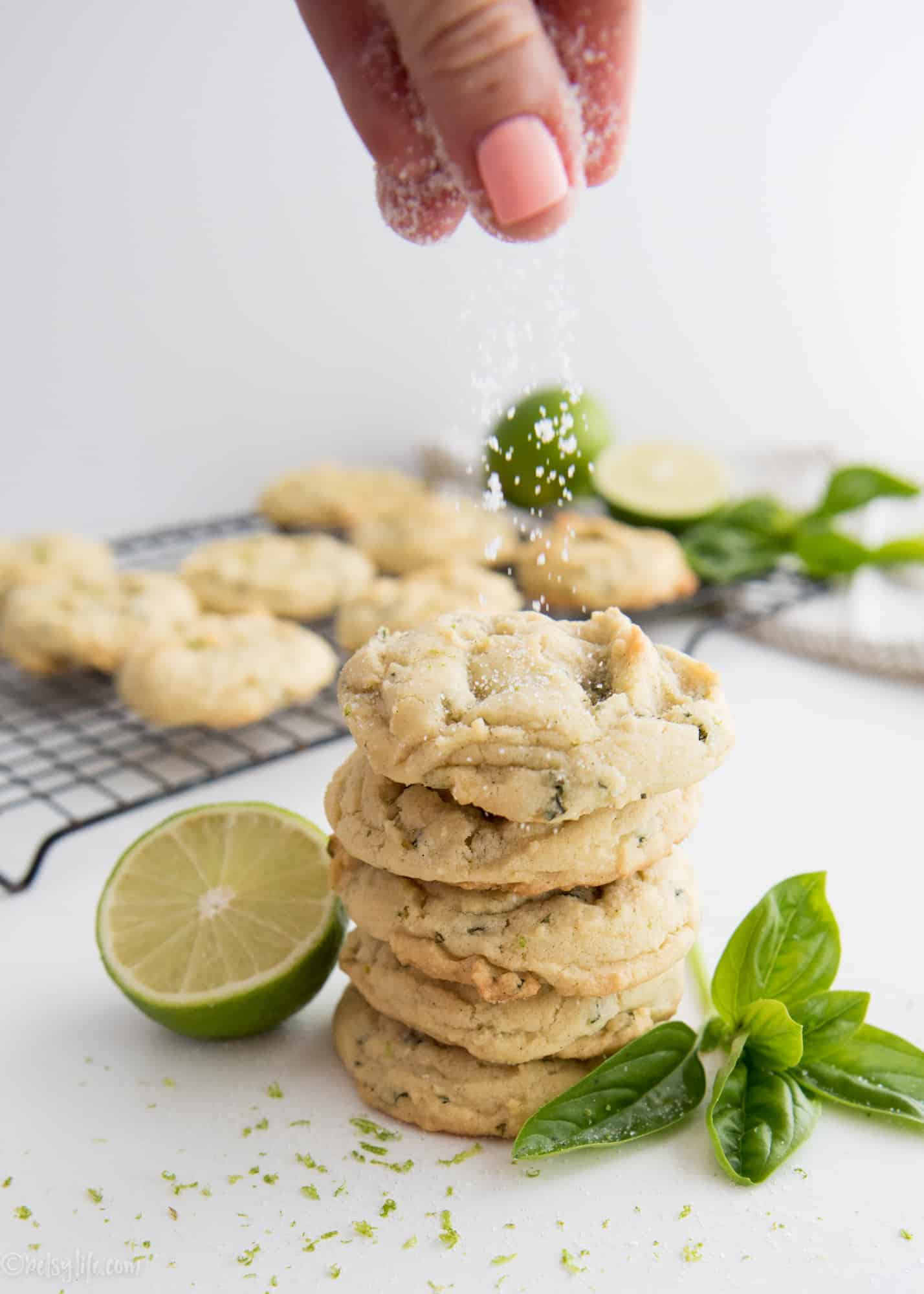 Fingers sprinkling sugar on a stack of basil lime sugar cookies