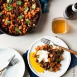 skillet of sweet potato and chorizo hash next to a plated serving topped with a poached egg