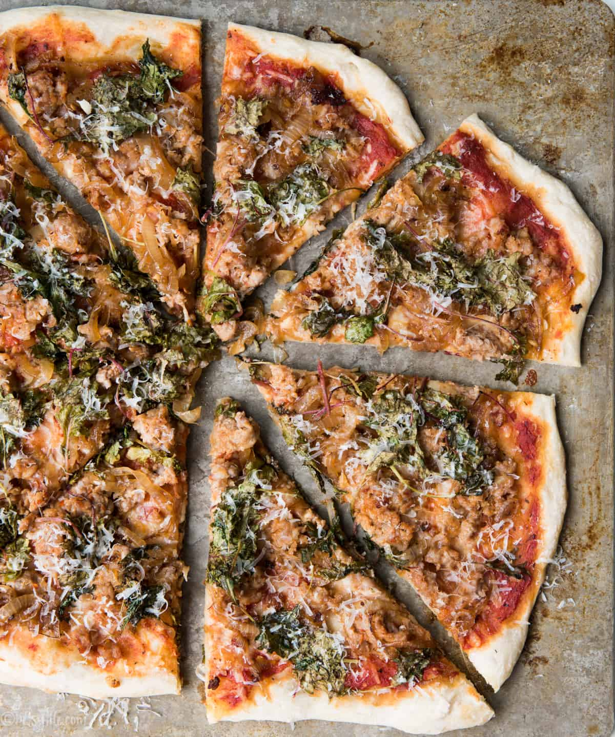 caramelized onion, kale and sausage pizza sliced into triangles on a baking sheet