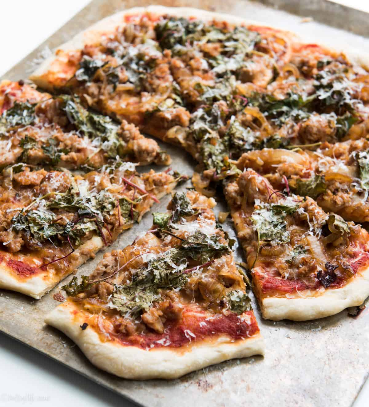 caramelized onion, kale and sausage pizza sliced on a baking sheet