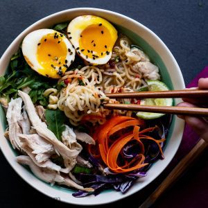 Bowl of leftover turkey soup with ramen noodles, runny egg, shredded carrots and greens